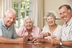 资深夫妇在家享受卡片的比赛小组 图库摄影