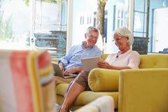 资深夫妇在家在使用数字式设备的休息室 免版税库存照片