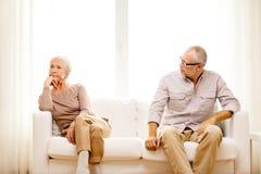 资深夫妇在家坐沙发 免版税库存图片