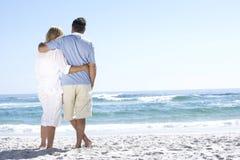 资深夫妇在度假走沿沙滩的看对海 免版税库存照片