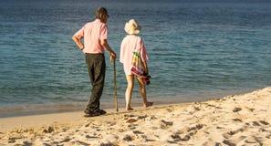 资深夫妇在海滩漫步 免版税库存图片