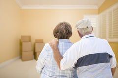 资深夫妇在看在地板上的屋子里移动的箱子 库存照片