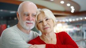 资深夫妇在购物中心神色站立在照相机 购物中心微笑的爱的拥抱的领抚恤金者 股票视频
