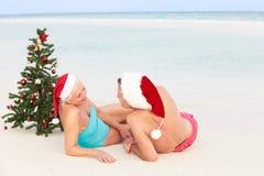 资深夫妇坐与圣诞树和帽子的海滩 免版税图库摄影
