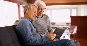 资深夫妇坐在片剂的长沙发观看的录影 免版税库存照片