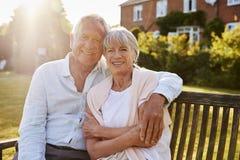 资深夫妇坐庭院长凳在晚上阳光下 库存图片