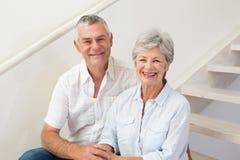 资深夫妇坐微笑对照相机的台阶 库存照片
