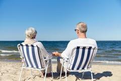 资深夫妇坐椅子在夏天海滩 图库摄影