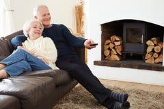 资深夫妇坐看电视的沙发 库存照片