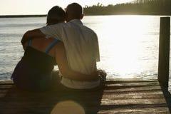 资深夫妇坐码头由湖 免版税库存照片