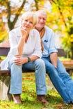 资深夫妇坐部分在秋天换下场 免版税库存图片