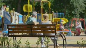 资深夫妇坐长凳在操场附近,观看的孙使用 股票视频