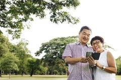 资深夫妇快乐的耳机机动性概念 库存照片