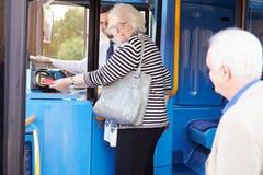 资深夫妇搭乘公共汽车和使用通行证 免版税库存图片
