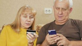 资深夫妇支付购买在互联网由银行信用卡 妇女口授数字,一个人进入 股票录像