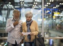 资深夫妇旅行的机场场面概念 库存图片