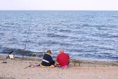 资深夫妇日间坐在一顿野餐的海滩与钓鱼竿由海 图库摄影