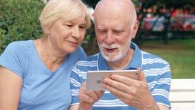 资深夫妇有了不起的时间坐长凳在公园聊天的放松,浏览在智能手机 股票录像
