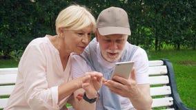 资深夫妇有了不起的时间坐长凳在公园聊天的放松,浏览在智能手机 影视素材