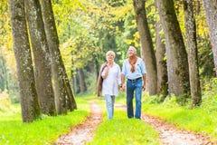 资深夫妇有休闲步行在森林 免版税库存照片