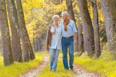 资深夫妇有休闲步行在森林 免版税图库摄影