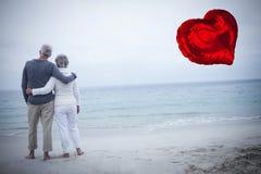 资深夫妇的综合图象在海滩的和红色心脏迅速增加3d 免版税库存图片
