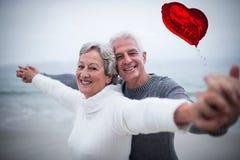 资深夫妇的综合图象在海滩的和红色心脏迅速增加3d 库存照片