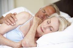 资深夫妇睡着的床 免版税库存照片