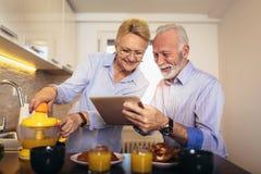 资深夫妇繁忙的看看数字片剂,当有可口早餐在家厨房时 免版税库存照片