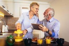 资深夫妇繁忙的看看数字片剂,当有可口早餐在家厨房时 库存照片