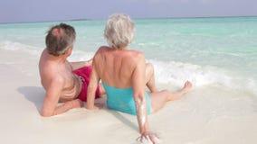 资深夫妇背面图坐美丽的海滩 图库摄影