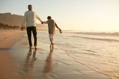 资深夫妇获得乐趣在海滩 免版税库存照片