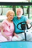 资深夫妇驾驶高尔夫车 免版税库存照片