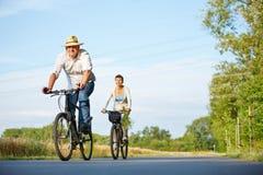 资深夫妇骑马自行车通过风景 免版税库存图片