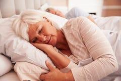 资深夫妇说谎睡着在床上一起 库存照片