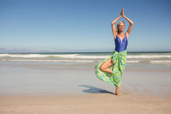 资深女子实践的瑜伽,当站立反对清楚的天空时 免版税库存图片