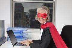 资深女实业家画象超级英雄服装的使用在办公桌的膝上型计算机 库存照片