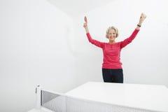 资深女性乒乓球球员画象有胳膊的提高了庆祝胜利 免版税库存照片