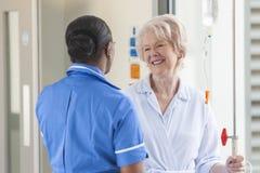 资深女性患者和护士在医院 免版税库存照片