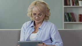 资深女性投入在玻璃和看片剂,读网上报纸 影视素材