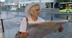 资深女性有一张地图的游人探索的镇在手上 寻找路线 影视素材