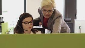 资深女性检查和给称赞年轻美丽的妇女在办公室