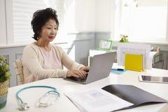 资深女性Working At Laptop In医生办公室 库存图片