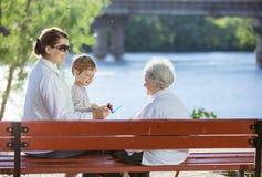 资深妇女、她的成人孙女和重孙子在公园 库存图片