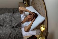 资深妇女不可能睡觉在夜间,当拿着她的头wi时 免版税库存照片