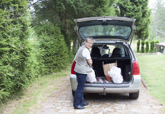 资深妇女举的袋子汽车 库存照片