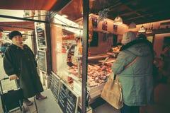 资深妇女买的烟肉和香肠在Viktualienmarkt的肉商店 免版税库存照片