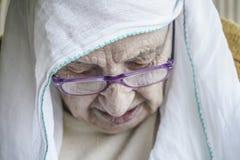 资深妇女佩带的头巾,当祈祷时 库存照片