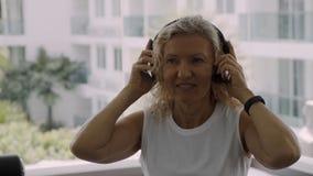 资深妇女参与健身房 听到在耳机的音乐的白肤金发的妇女在健身房 库存图片