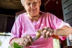 资深妇女发隆隆声的土豆 免版税库存图片